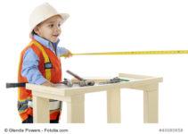 Ein Junge steht an der Werkbank für Kinder und misst etwas aus.